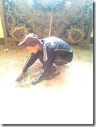 أحد الطلاب ينظف مدخل مصنع بالمنطقة